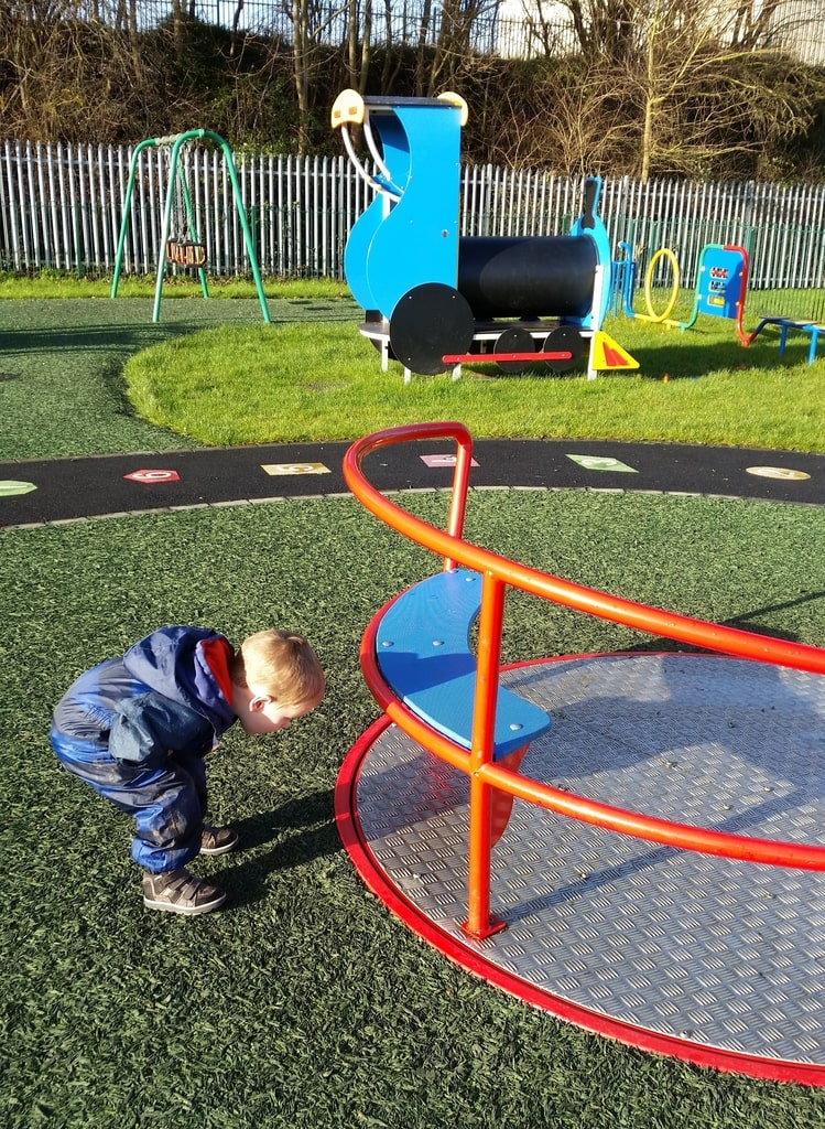 boy looking at roundabout spin