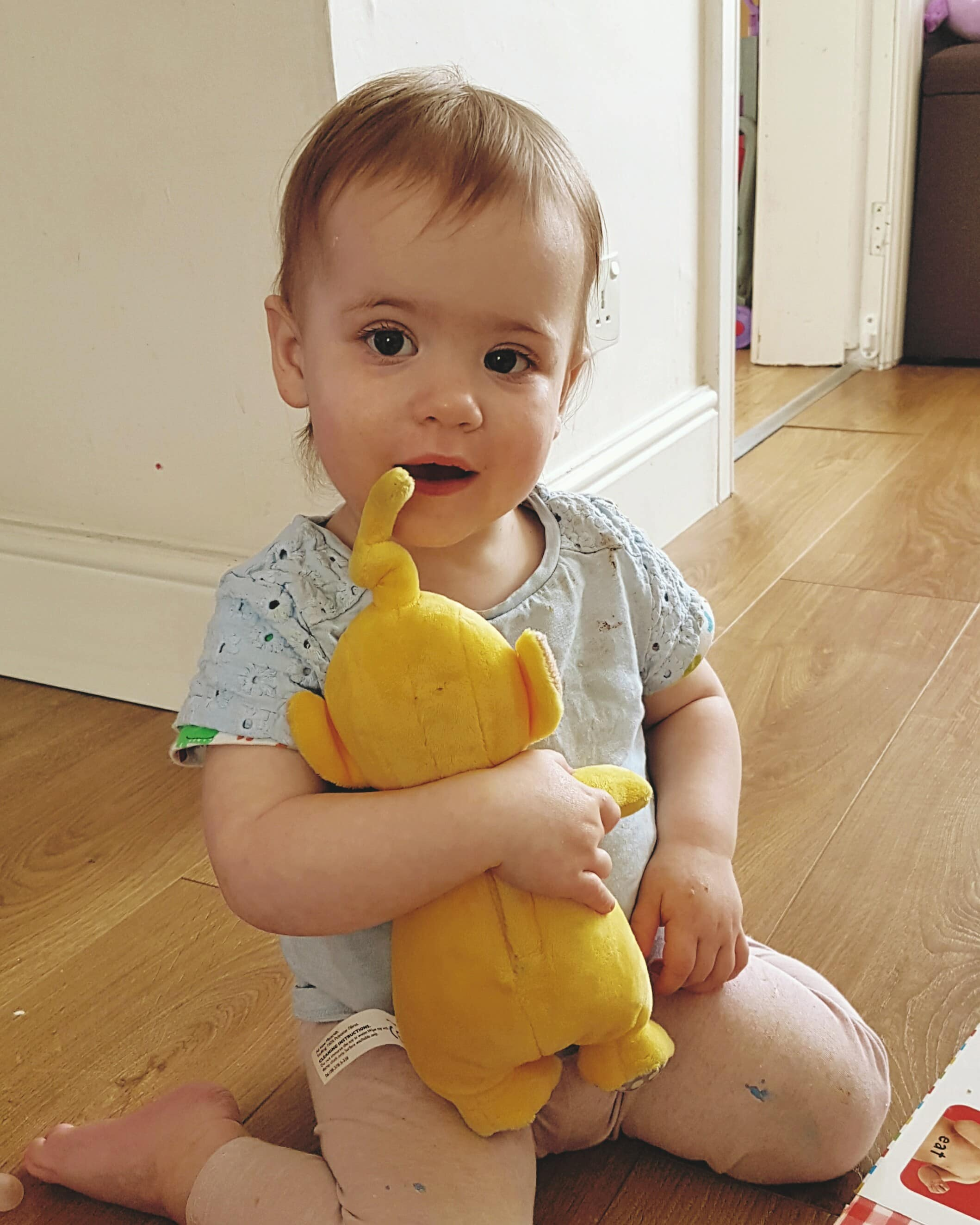 baby holding yellow teletubbies toy