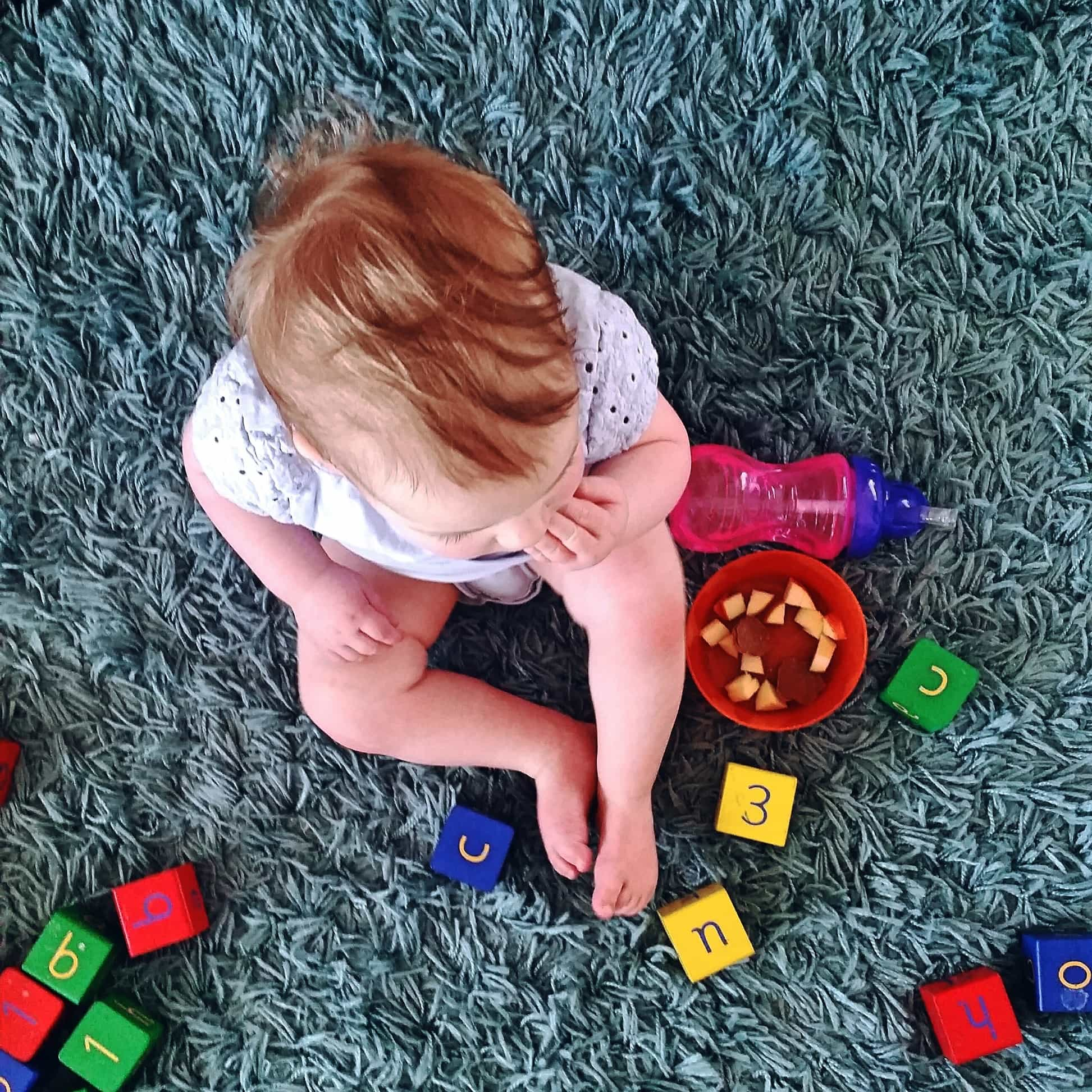 Baby from above with blocks and straw cup next to her