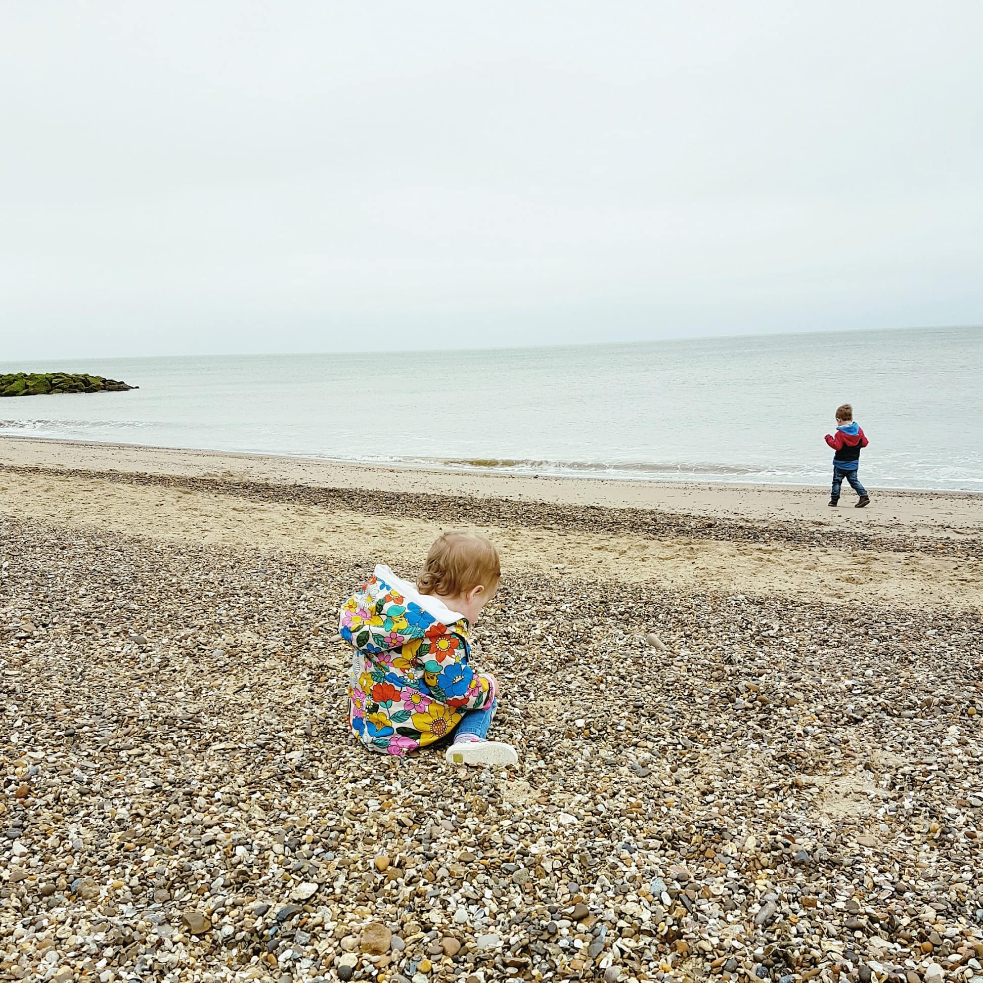 A baby plays on the beach with a toddler in the distane