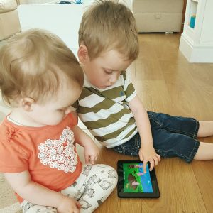 Small girl and boy using Kindle to view nursery rhyme app
