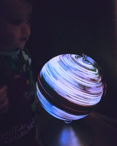 Boy looks at lit-up, spinning globe