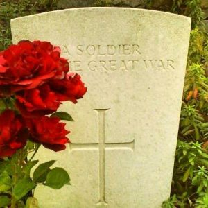 First World War gravestone with red flowers