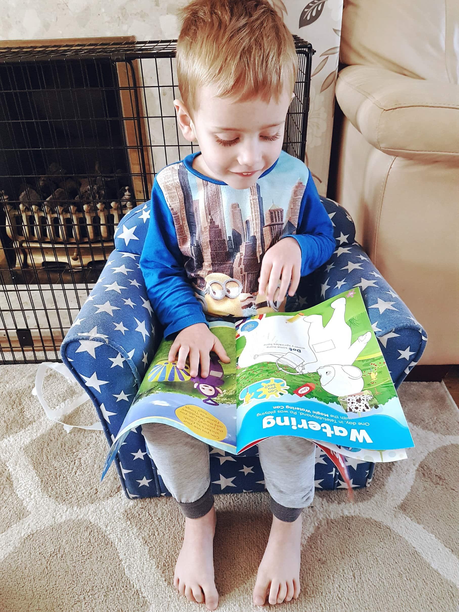 Boy reading Teletubbies magazine by Somoene's Mum
