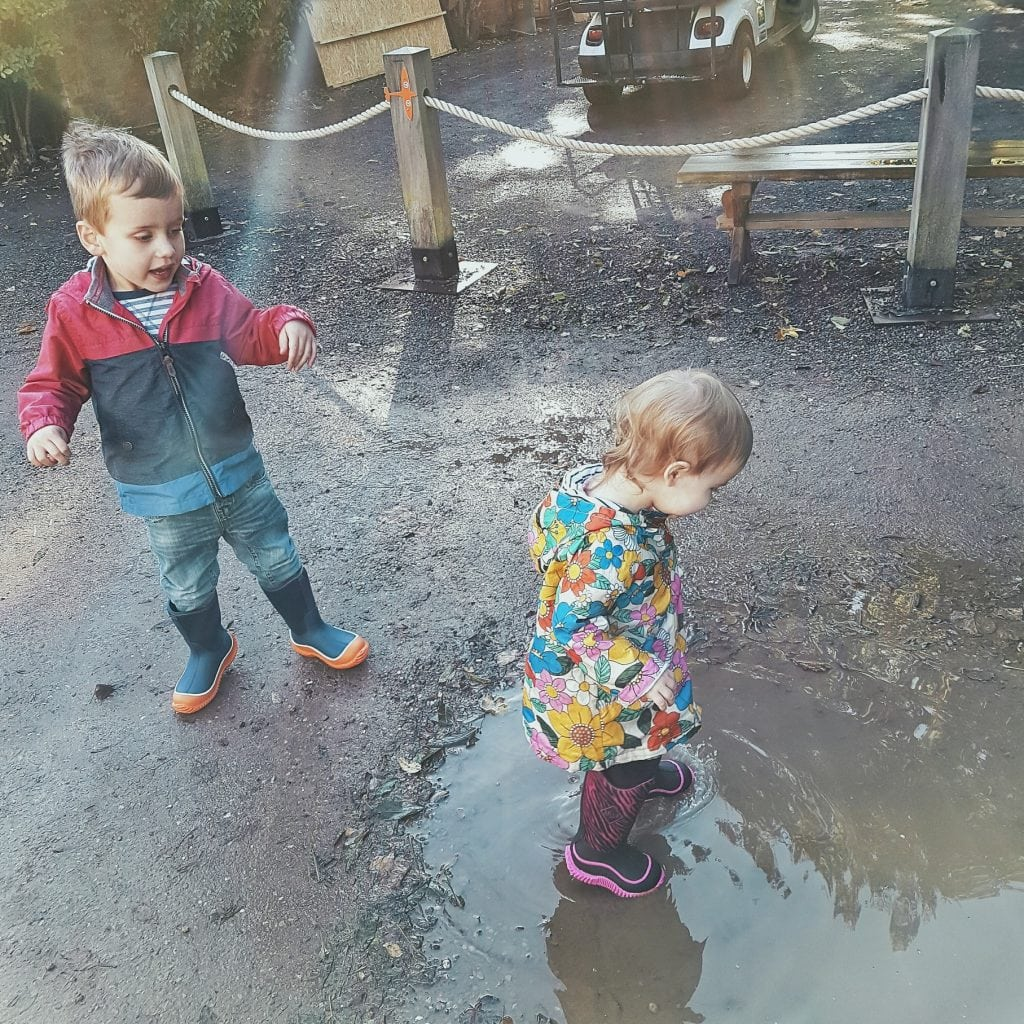 Little boy and little girl splashing in a puddle while wearing Muck Boots by Someone's Mum