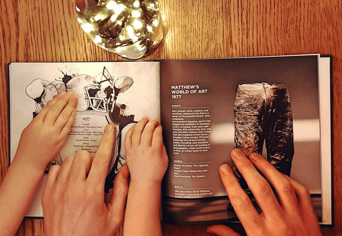The book of everyone - personalised book. With father and children's hands looking through. Photo by Someone's Mum