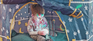 Boy with sensory toy in a tent. A Guide to Supporting Autistic Children at Christmas