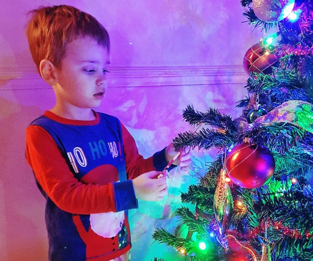 Boy looking at Christmas Tree in Mothercare pyjamas - Christmas traditions