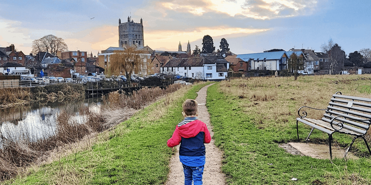 A young boy running along a river with a cathedral in the background.