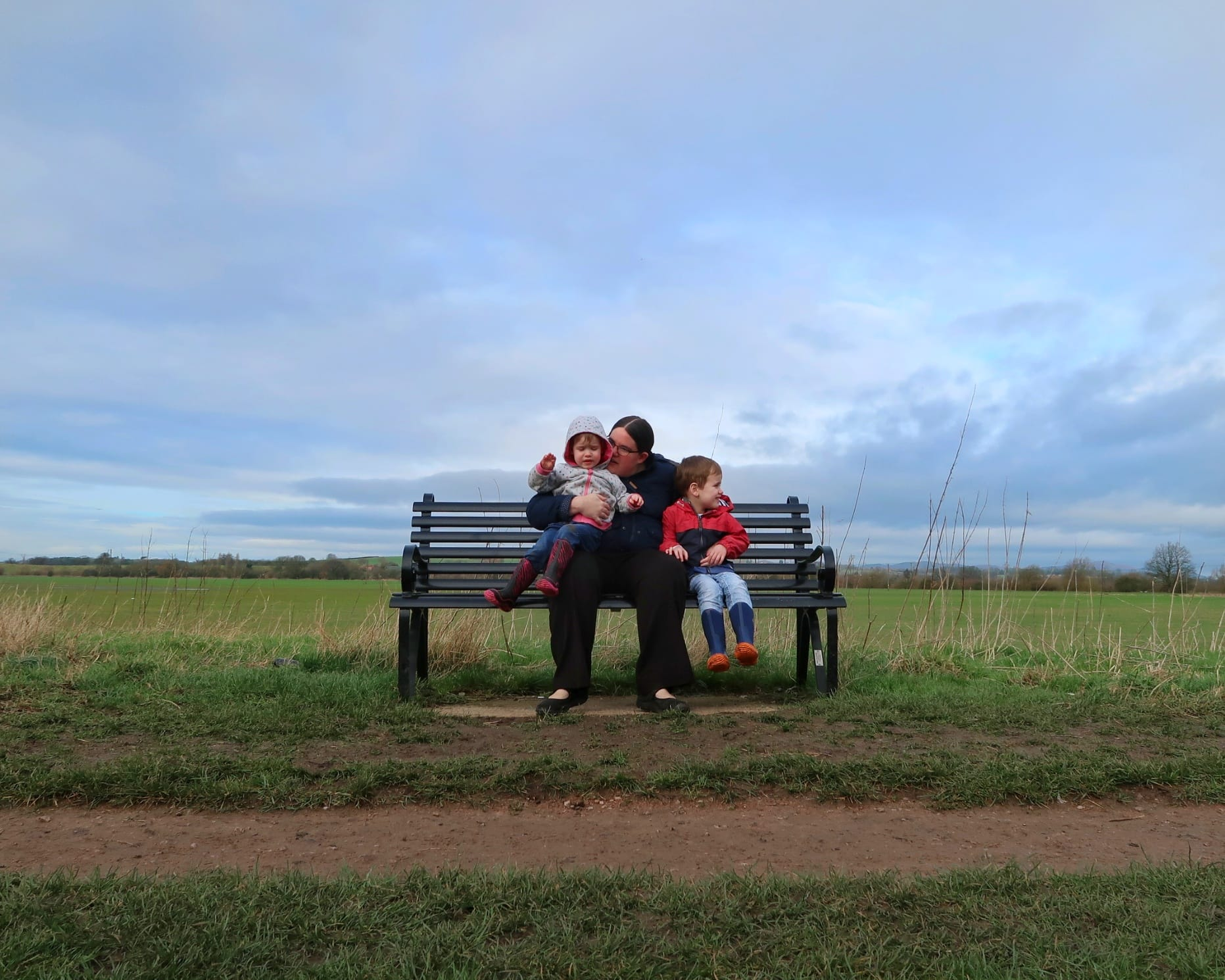Me and the children on a bench with a dramatic sky behind