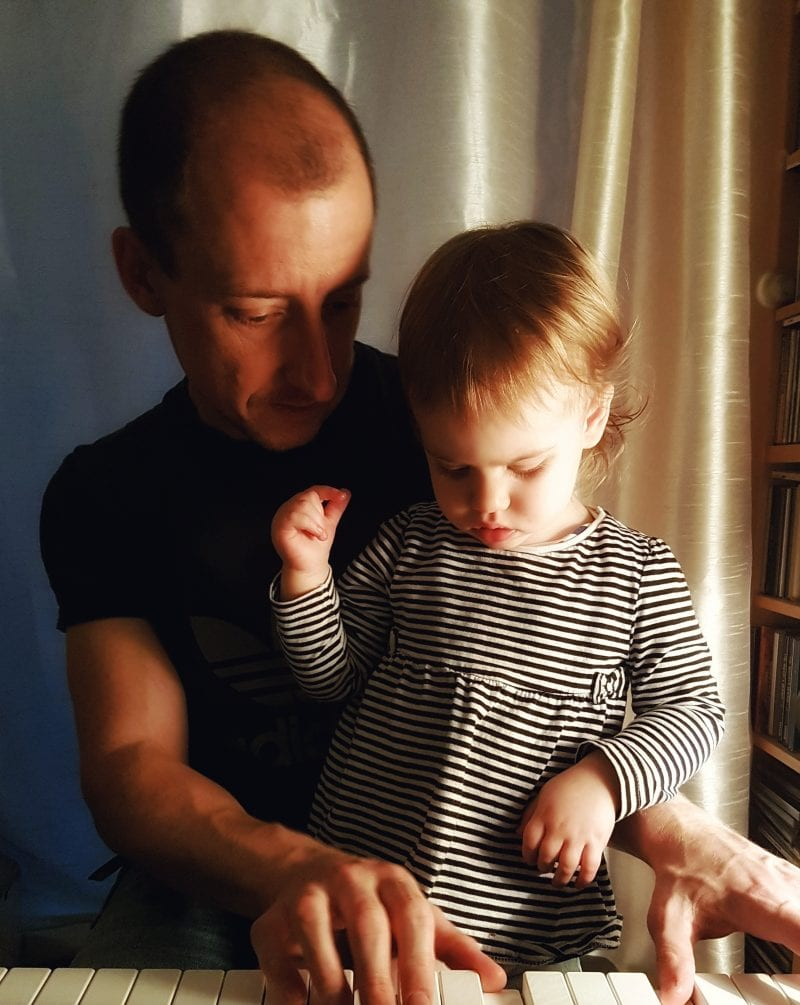Daddy playing the piano with baby daughter