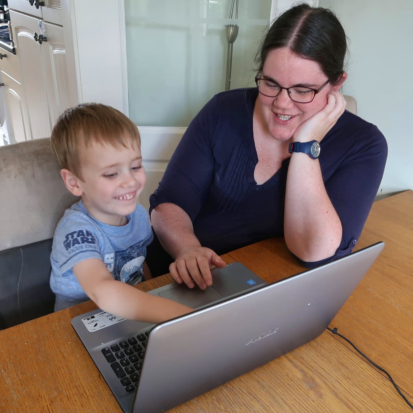 A boy and his mother at a laptop. Both are smiling and the boy is pointing. -Learning to read with Reading Eggs