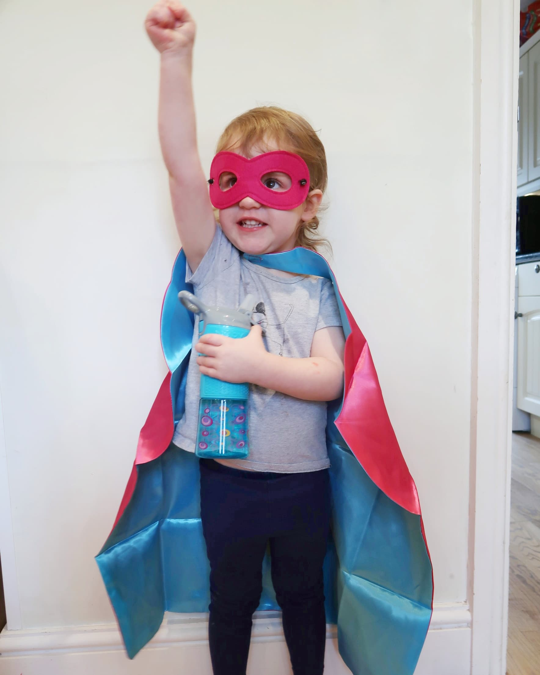 Littlest as a superhero with her Nuby Thirsty Kids cup