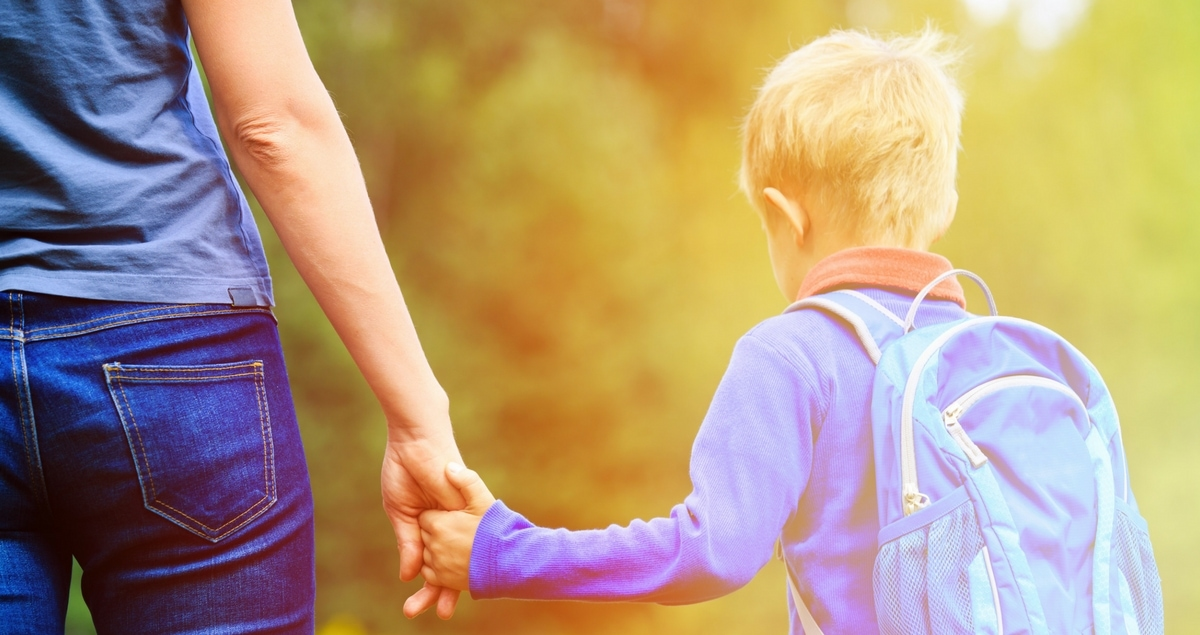 What I want the other parents to know as my autistic son starts school - boy holding hands with mother