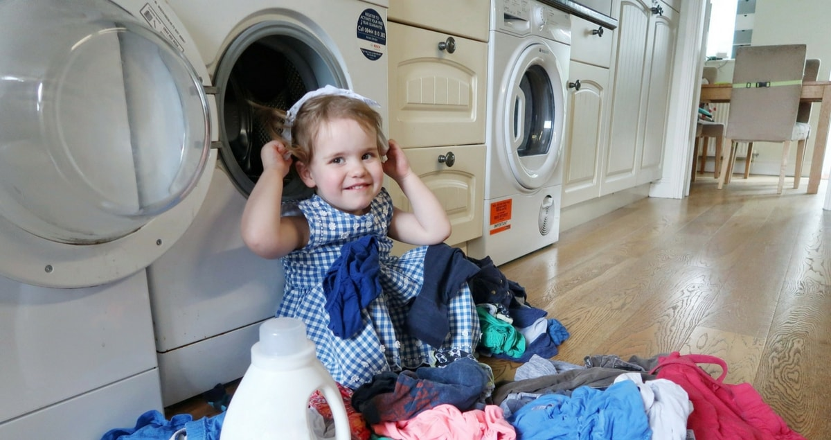 Which? magazine special offer - Littlest in front of washing machine with laundry.
