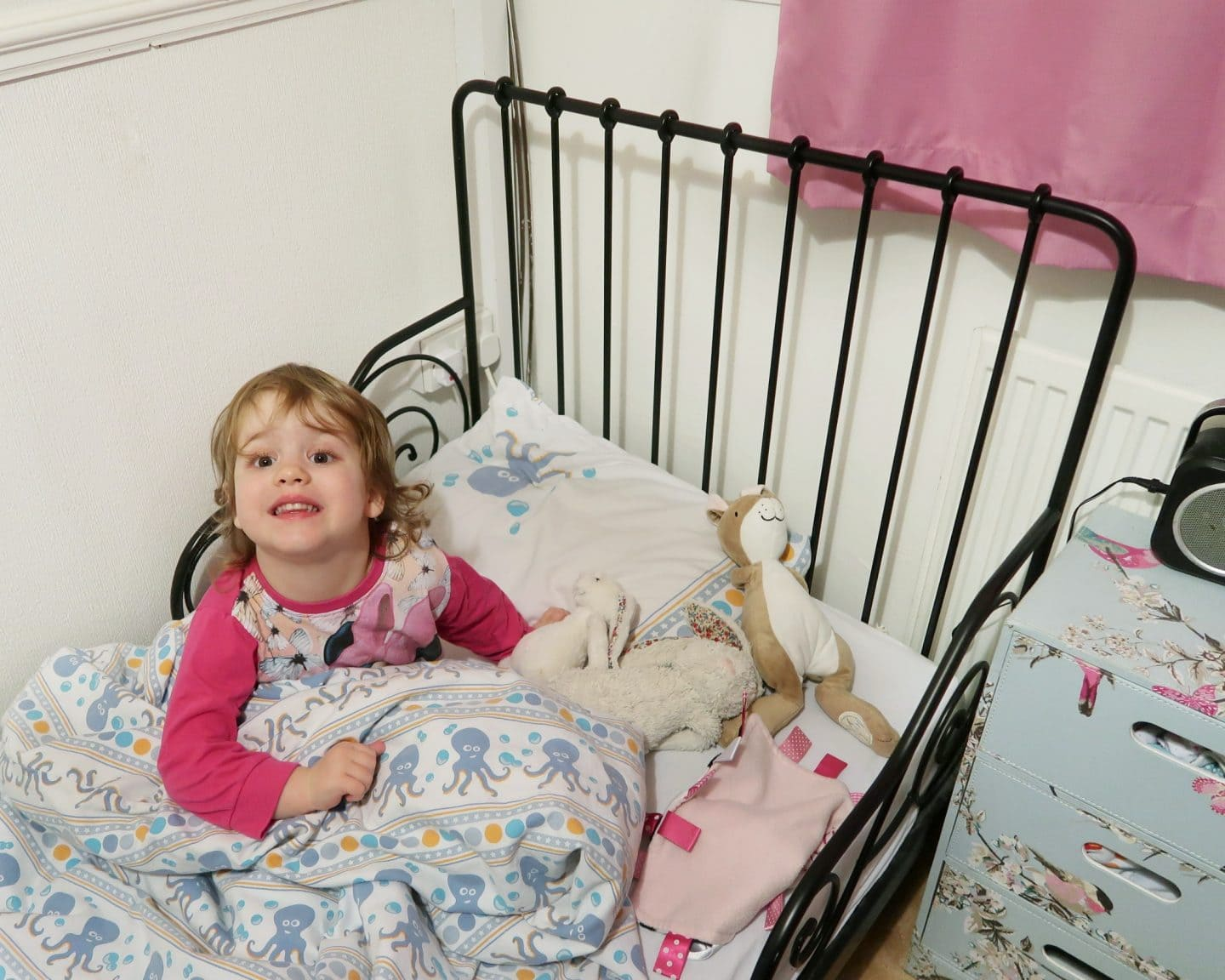 A little girl in her toddler bed surrounded by stuffed animals - for night time potty training tips