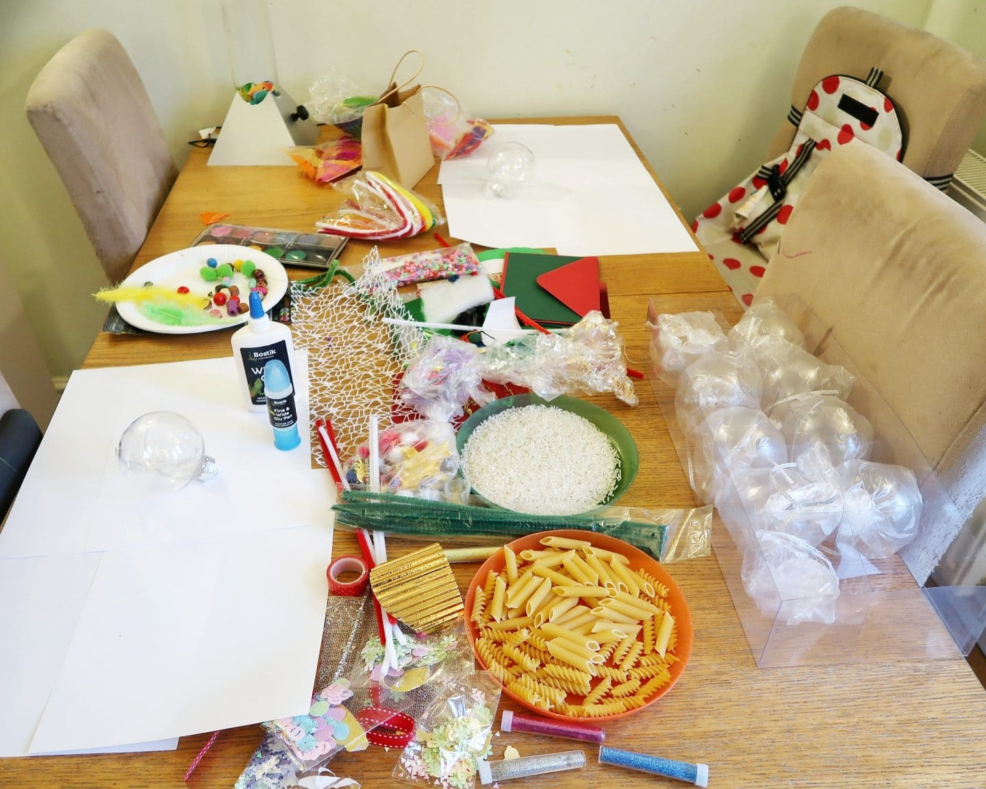 Lots of crafting materials like coloured card, glitter and sequins, all laid out on a table for Christmas Sensory bauble craft.