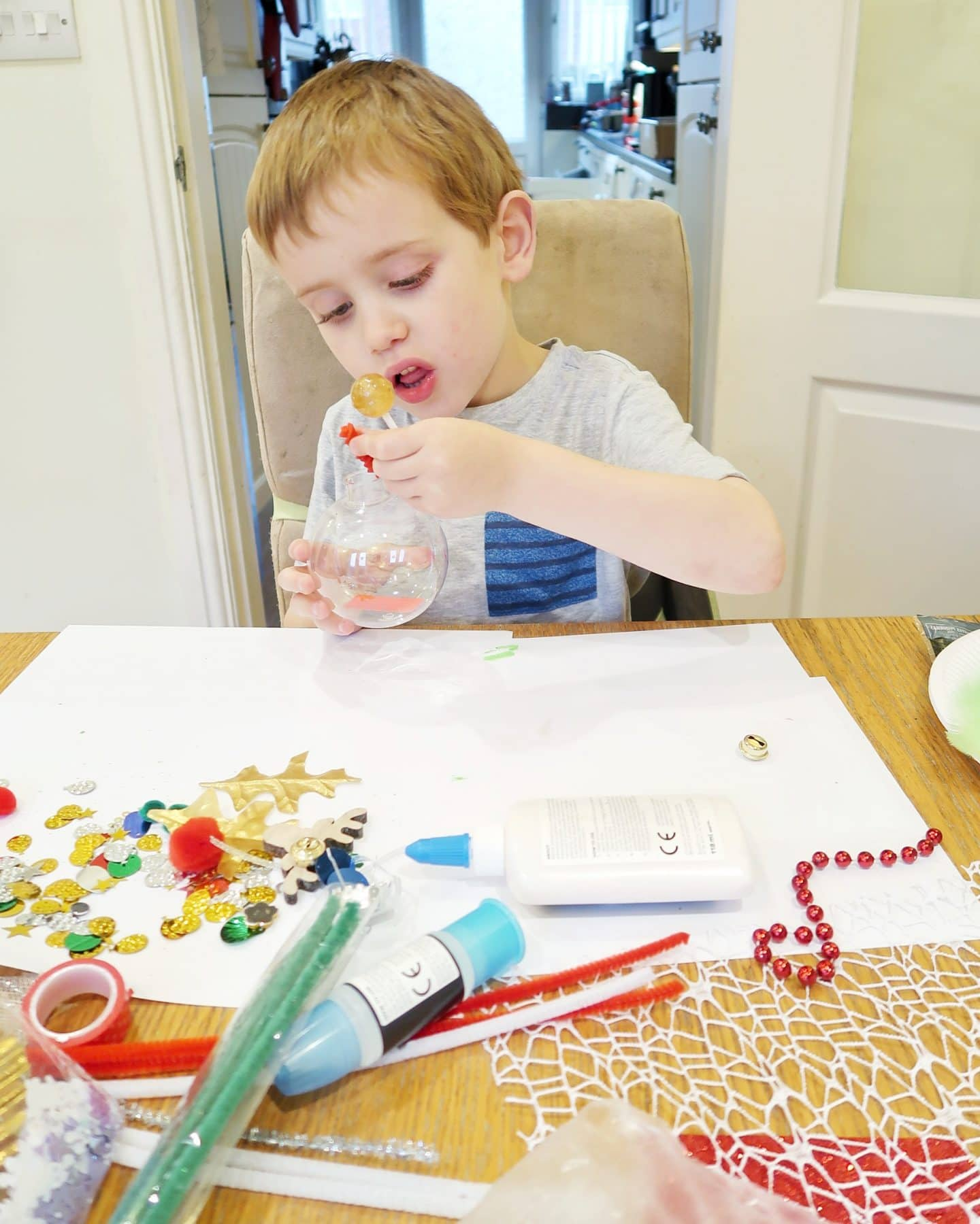 A small boy putting items into a clear plastic bauble - sensory bauble craft