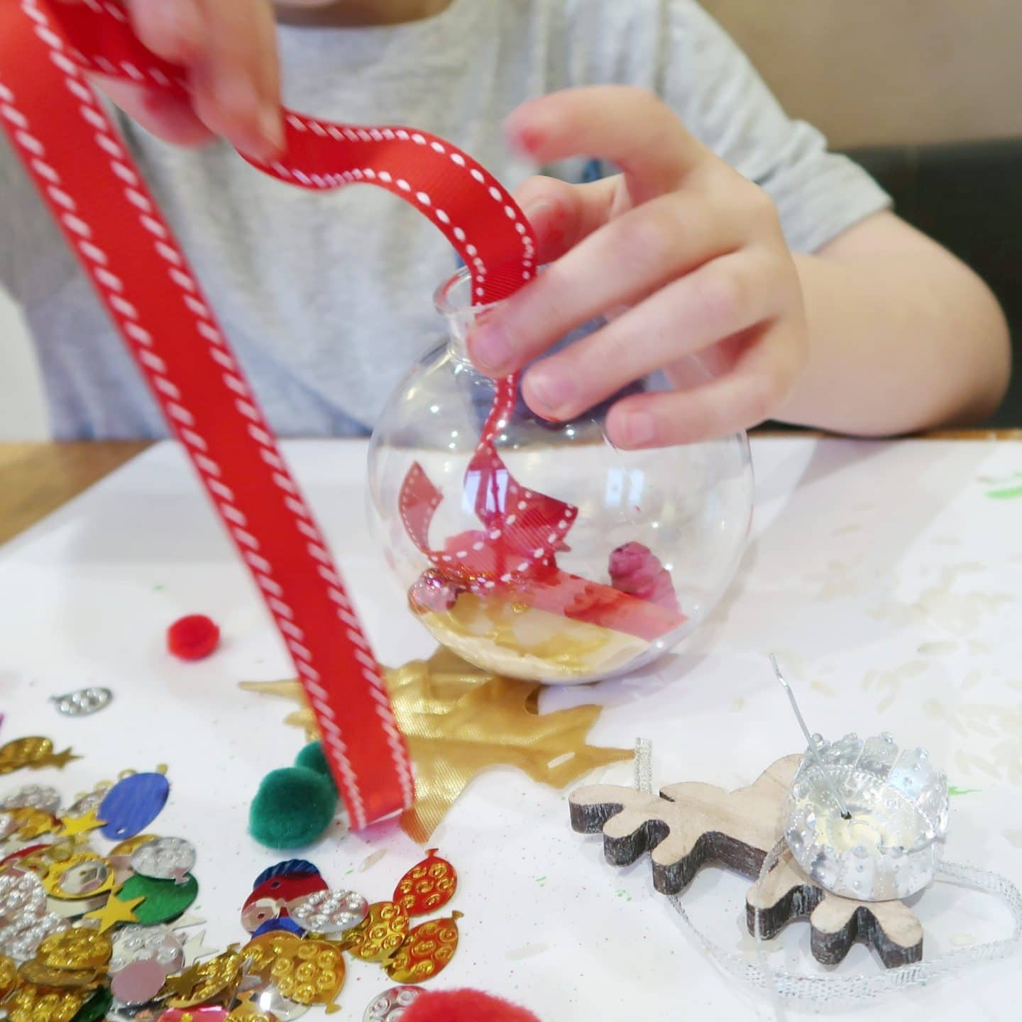 Boy threading a red ribbon into a clear plastic bauble - for sensory bauble craft