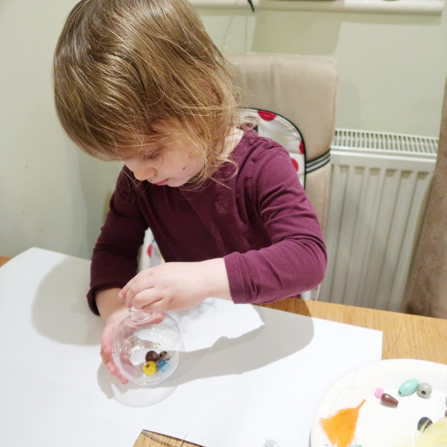 Small girl threading beads into a clear plastic bauble - for sensory bauble craft