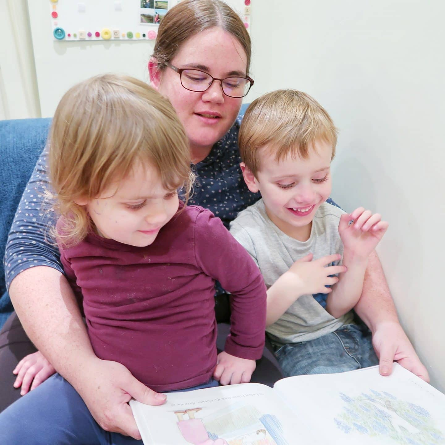 Mother and children, a small girl and boy, reading the book Katinka's Tail by Judith Kerr