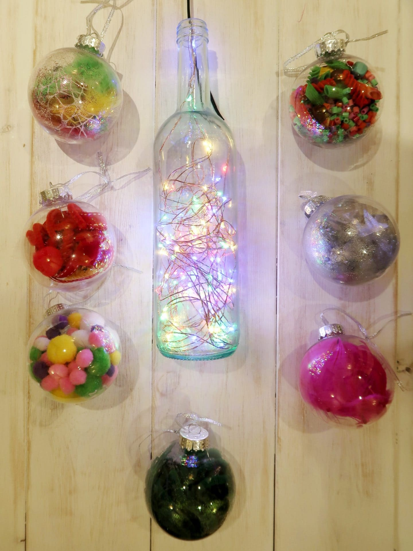 A selection of Christmas baubles with a wine bottle filled with coloured fairy light in the middle