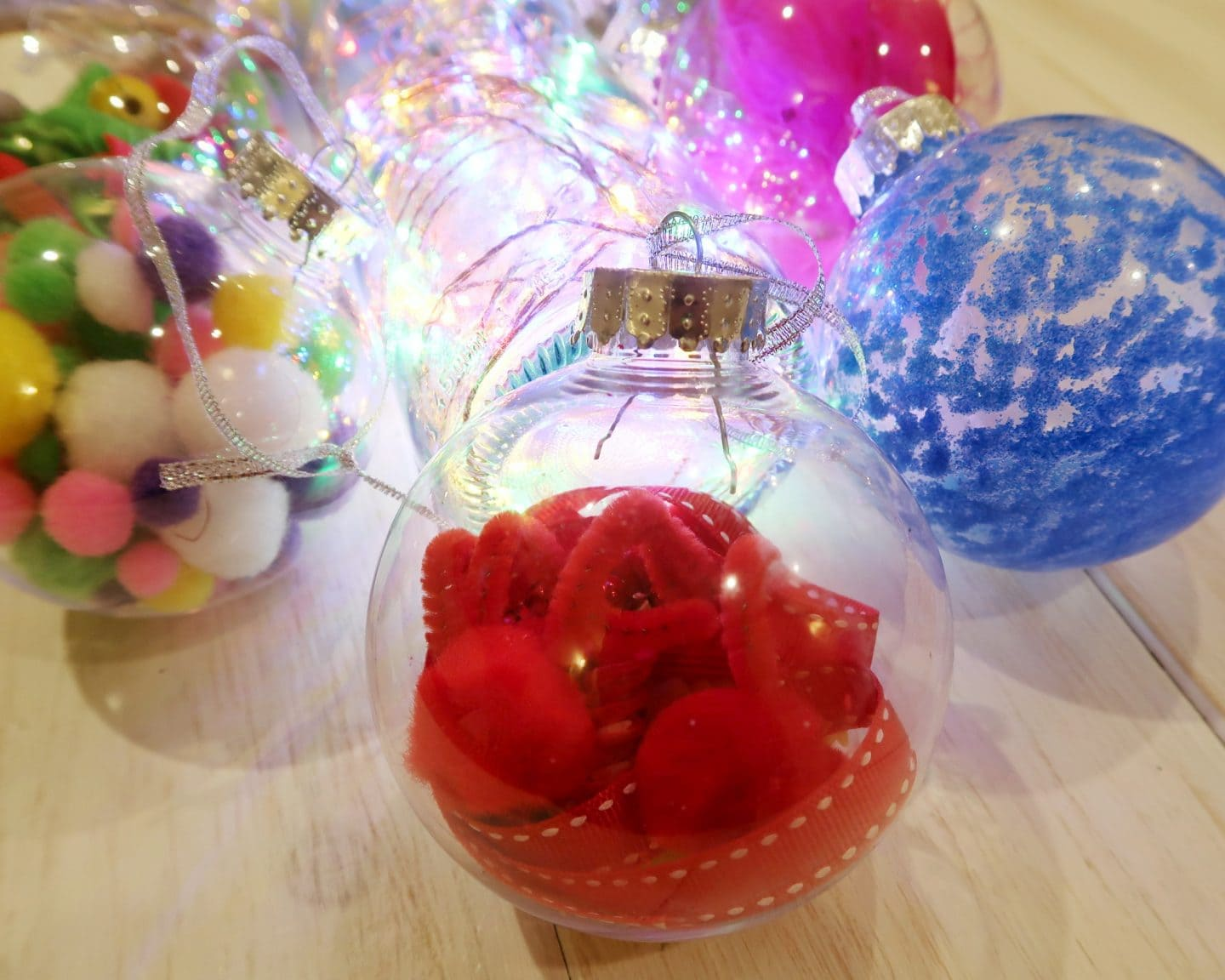 Bauble made with red pom poms, pipe cleaners and ribbon