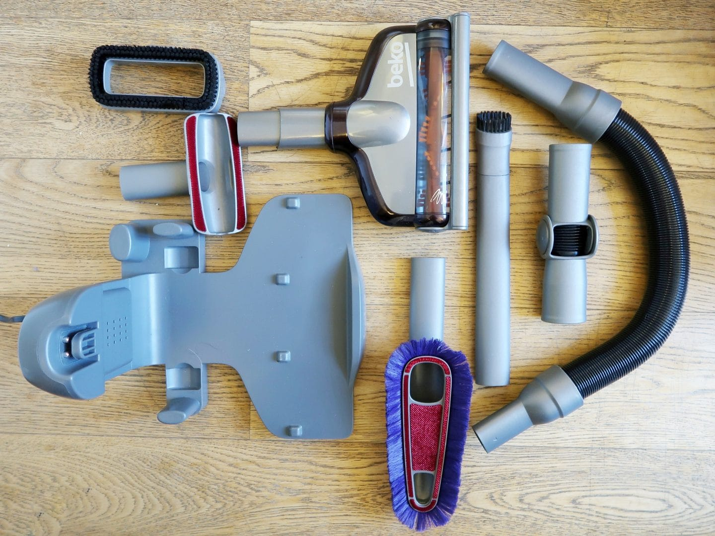 All the different attachment parts of the Beko Cordless vacuum arranged on the floor.