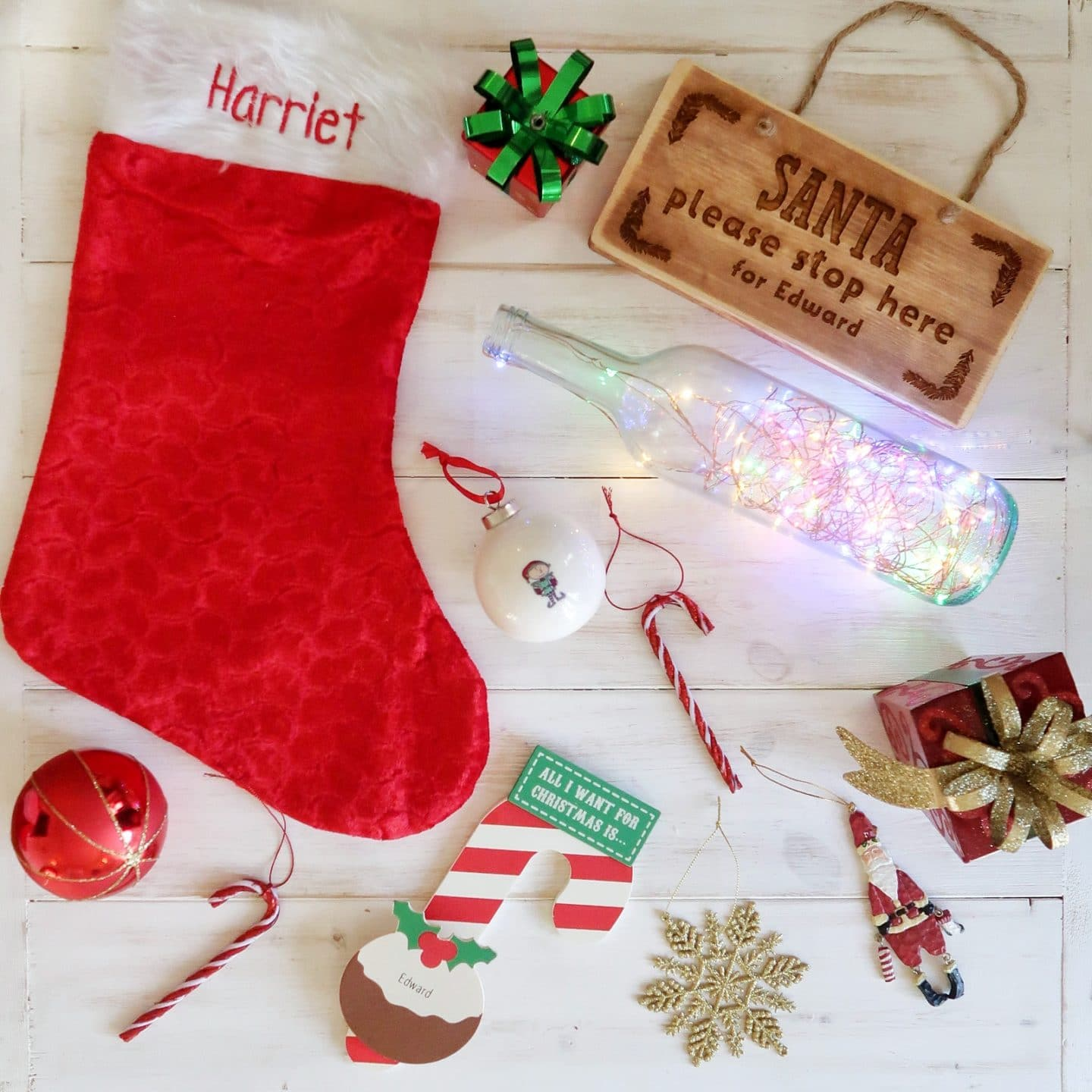 A selection of personalised Christmas Keepsakes, including a stocking, baubles and Santa stop here sign.