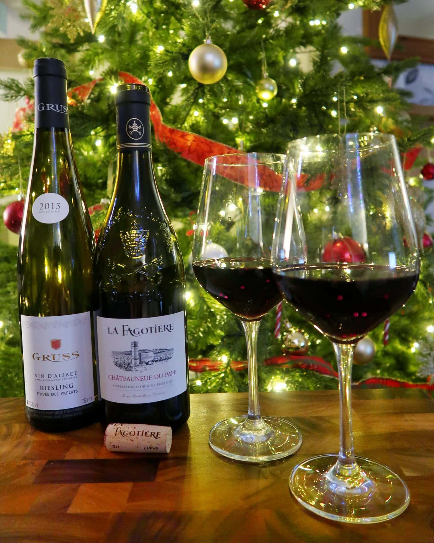 A selction of wine and glasses filled with red wine in front of a Christmas tree