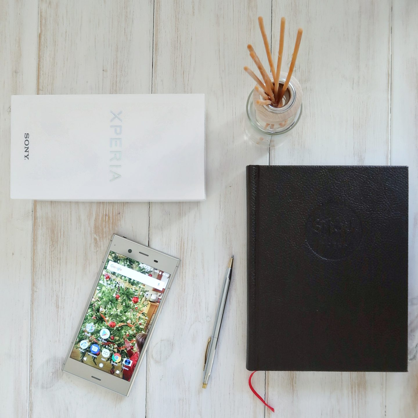 A flat lay image of the Sony Xperia ZX1, a diary, pen, and box.