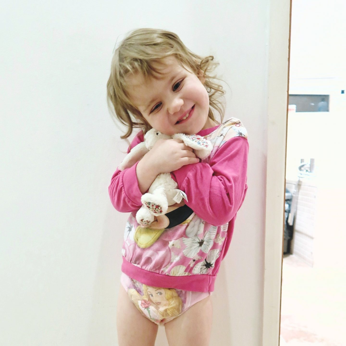 Little girl in pyjamas hugging a stuffed rabbit - tips for night-time potty training