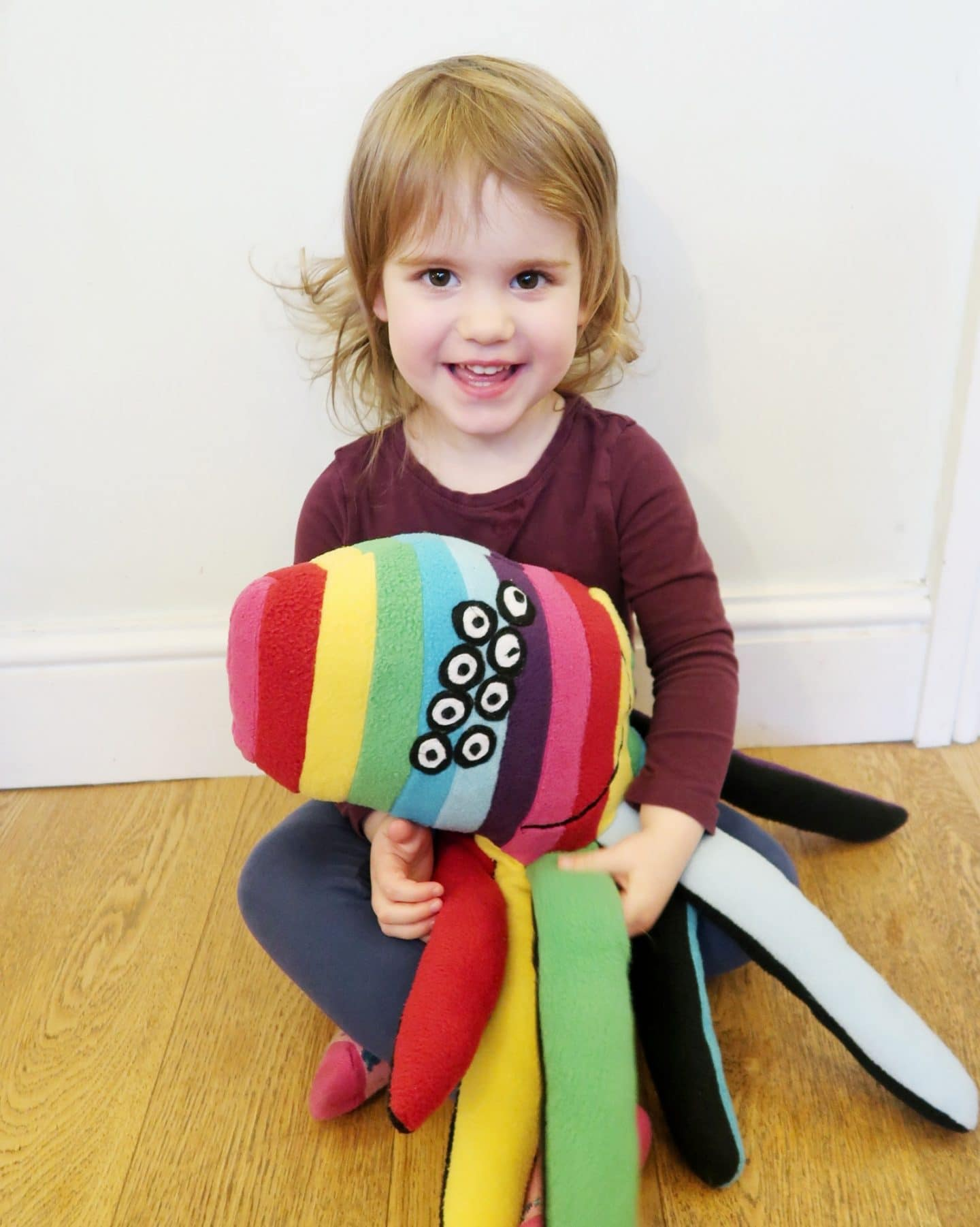 A small girl with a large rainbow spider soft toy