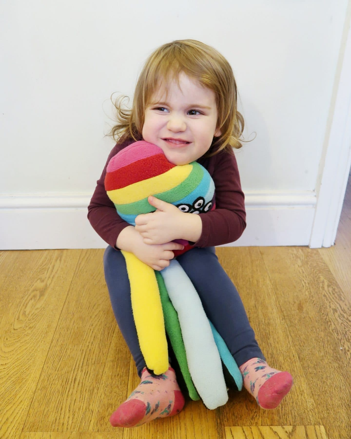A girl hugging a rainbow spider soft toy
