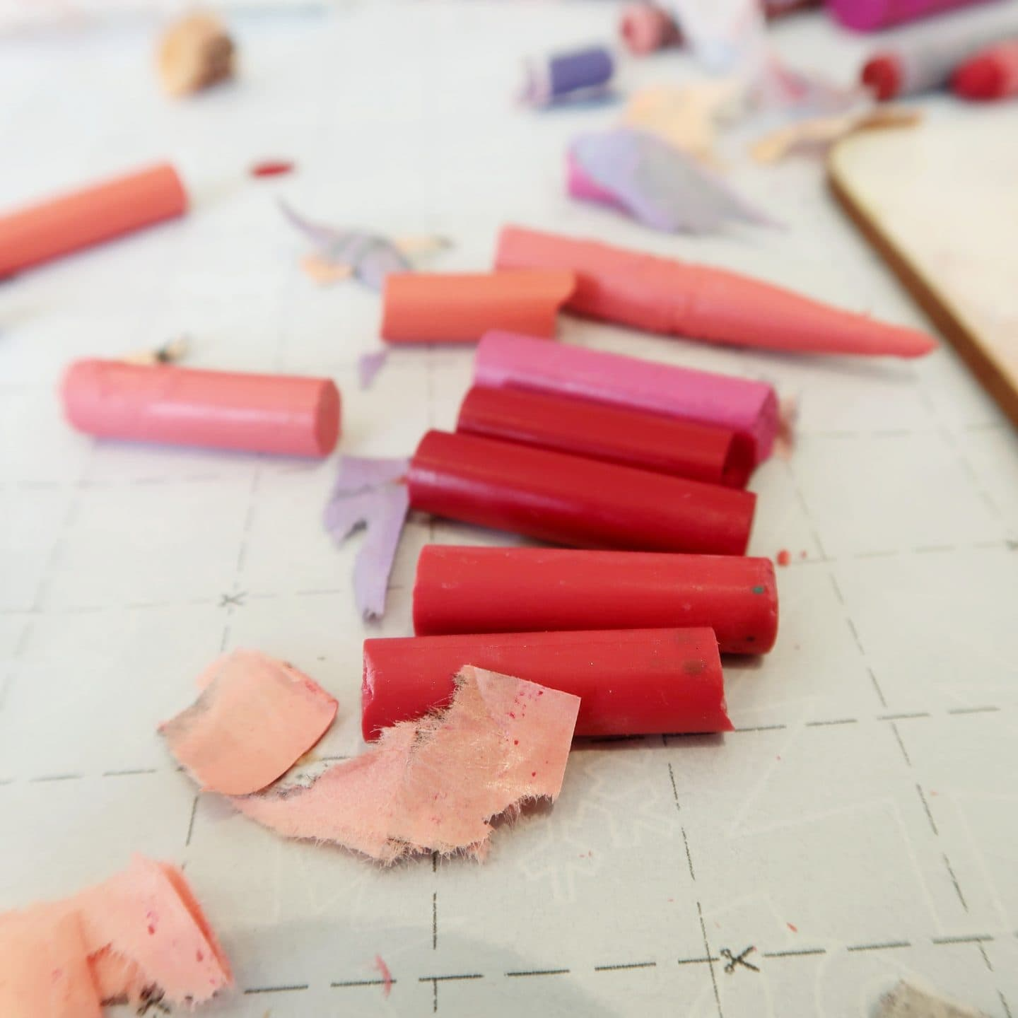 Close up of broken wax colouring crayons in pink and red.
