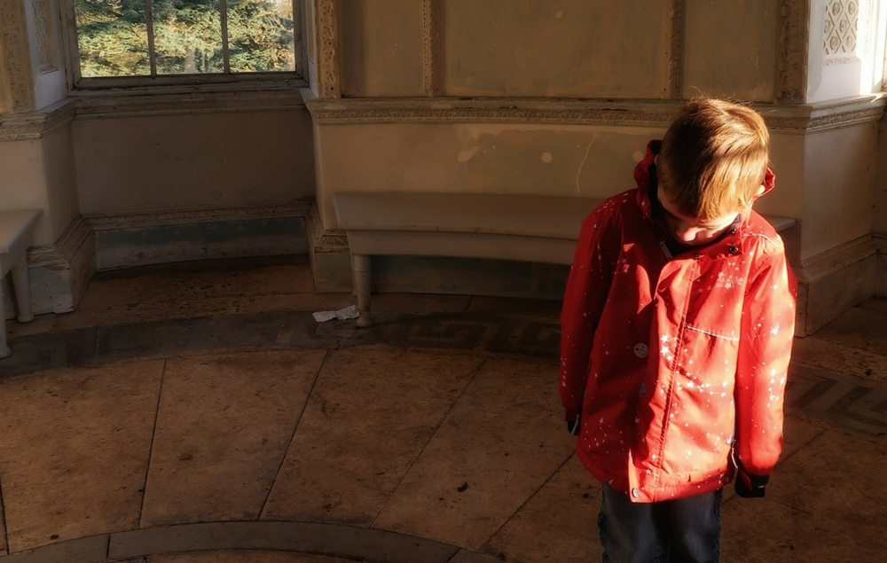 A small boy in a rotunda with sunlight streaming in. He is looking down, so his face is in shadow.