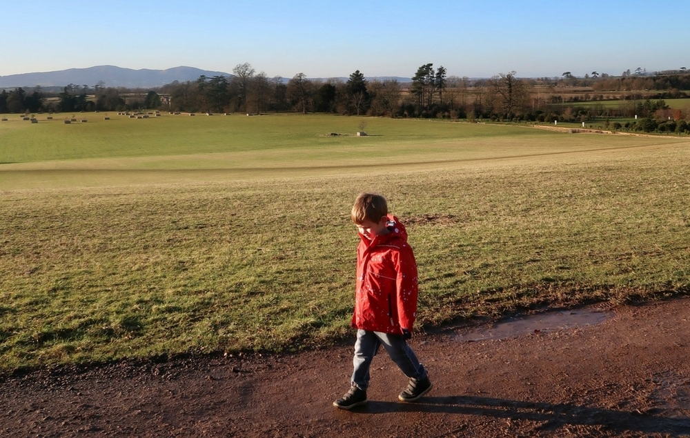 Boy walking with blue sky and green fields. Hills in the background - for It's not enough.