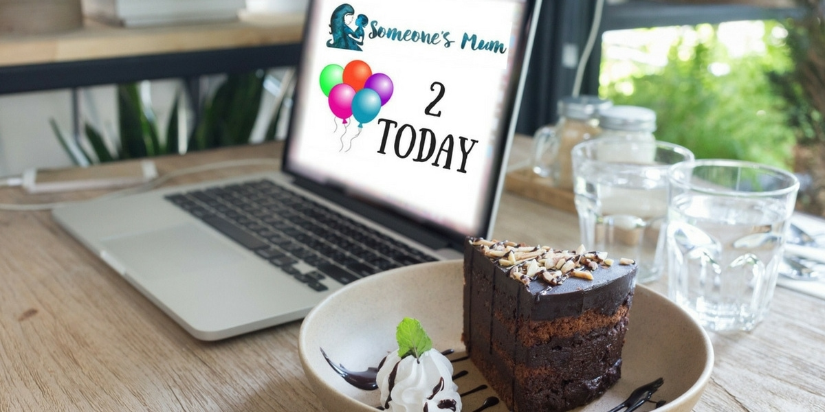 "Computer showing text ""Someone's Mum 2 Today"" with cake in foreground."