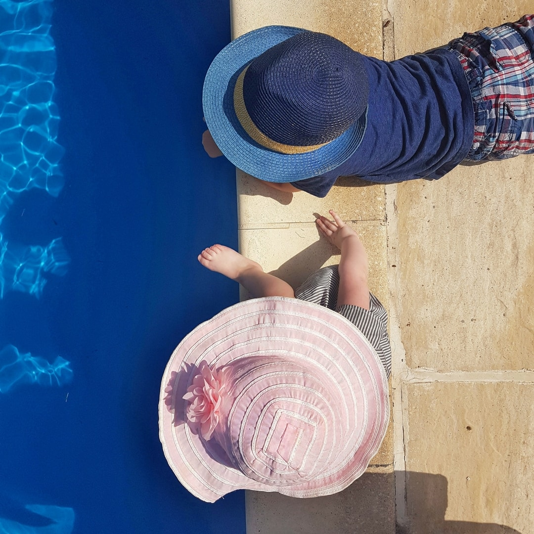 Boy in blue and and girl in pink hat, overlooking a pool from above.