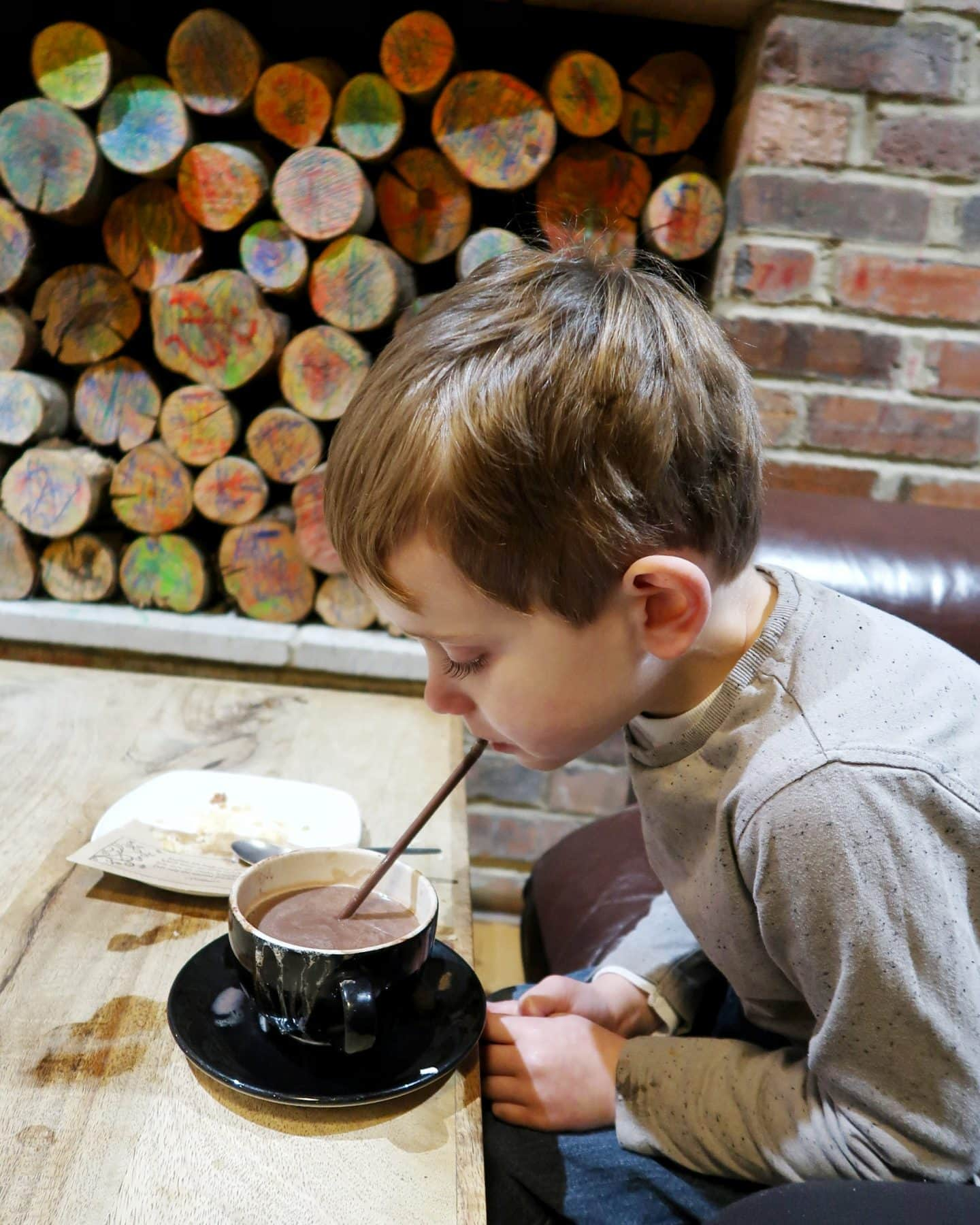 Boy drinking hot chocolate from a straw