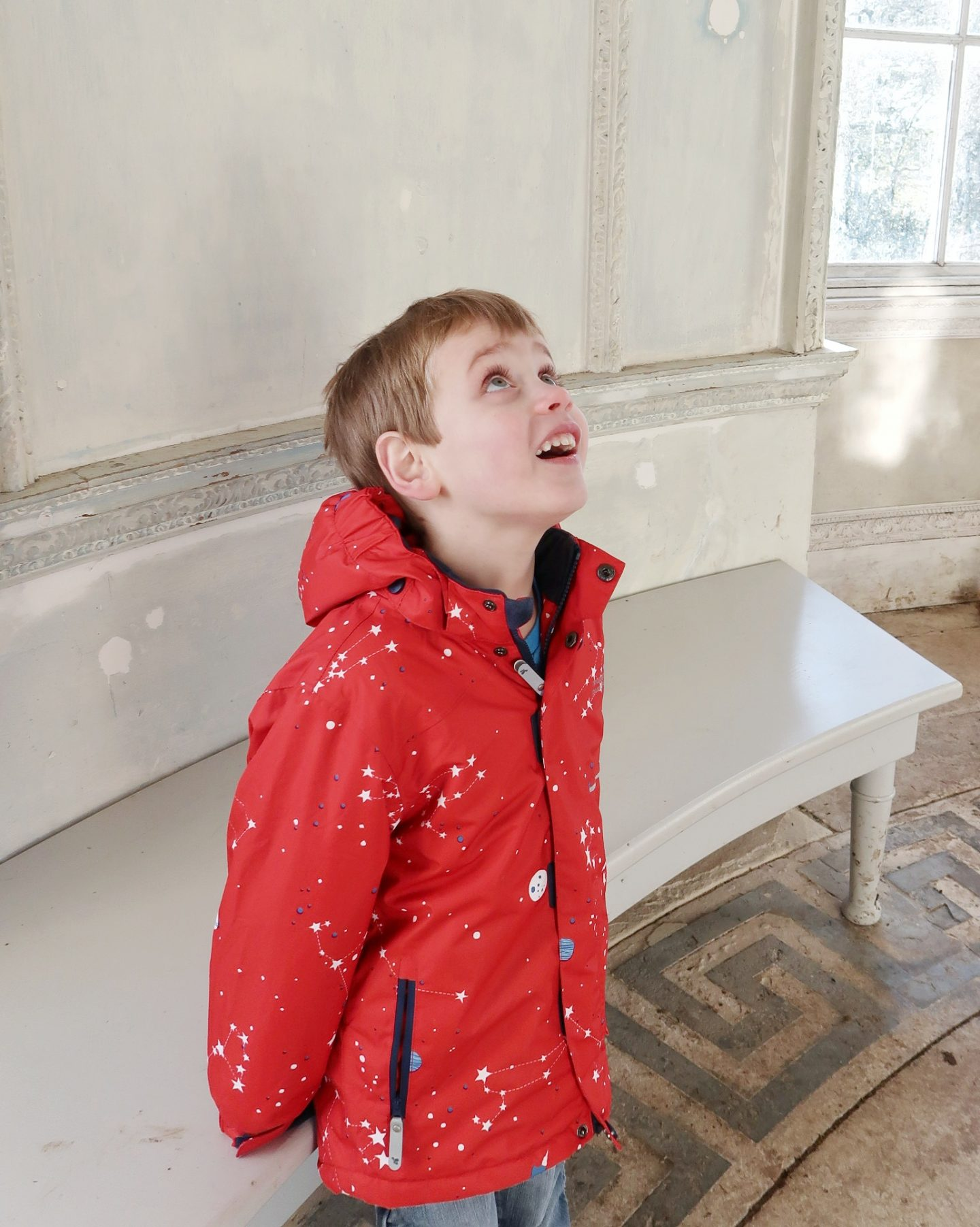 Small boy looking up at ceiling and smiling in the Rotunda at Croome - assumptions about autism