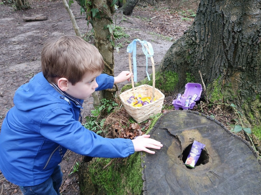 Small boy reaching for Cadbury Chocolate eggs to place in his Easter hunt basket