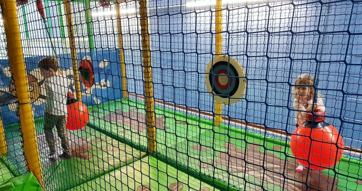 A boy and a girl playing at soft play and moving giant balls.