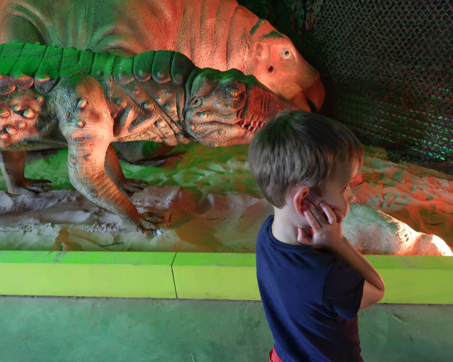 Biggest (a small boy) covering his ears in front of a model dinosaur.