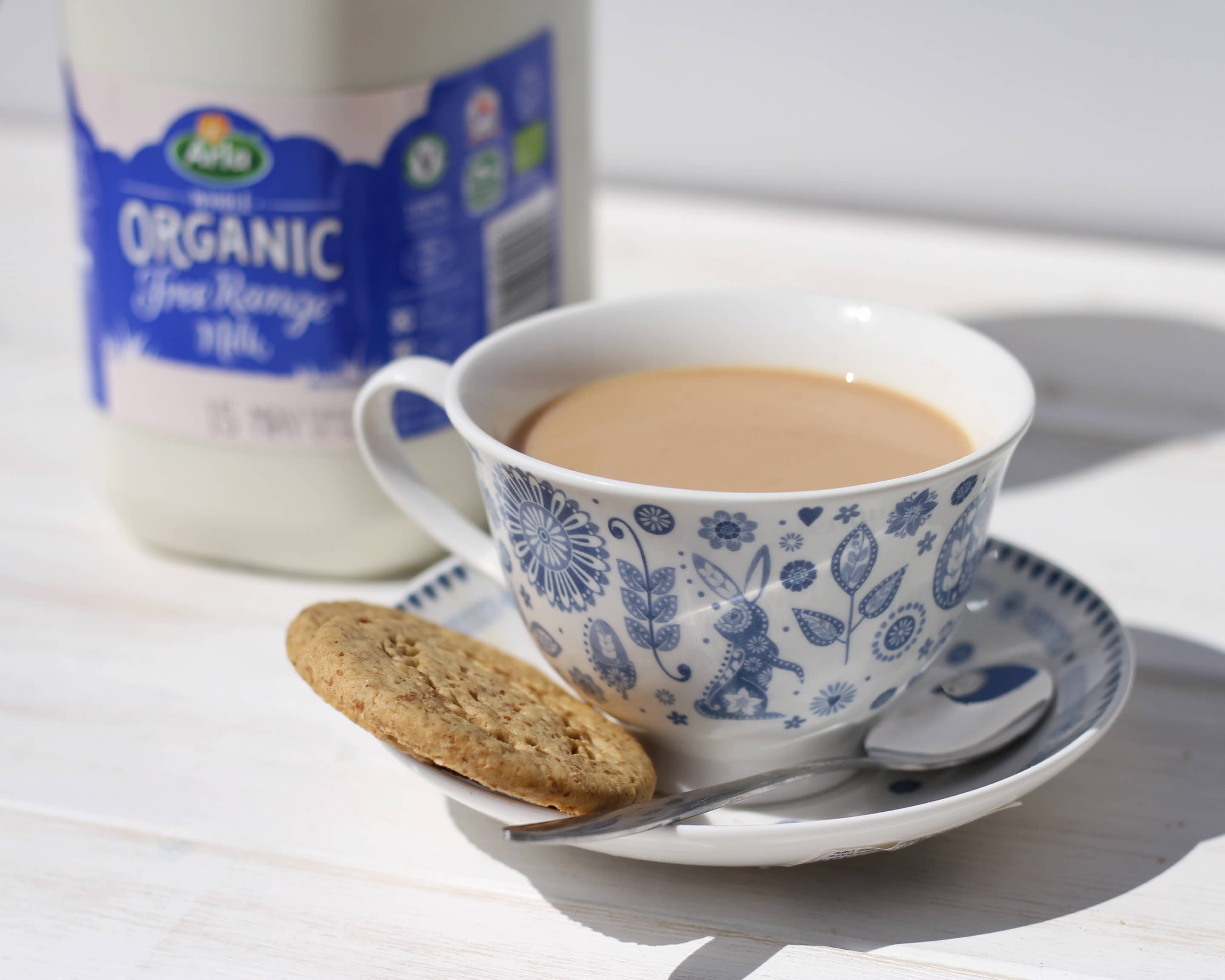 Tea in teacup with biscuits and Arla organic milk in the background