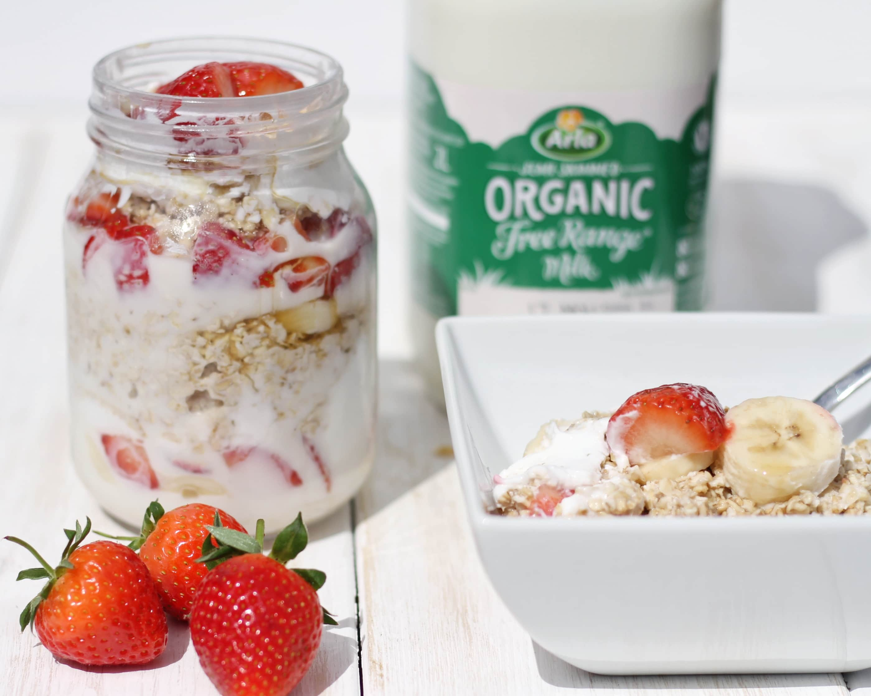 Overnight oats with Arla organic milk - a jar full of fruit and oats with a serving in a bowl and organic mlik carton in the background