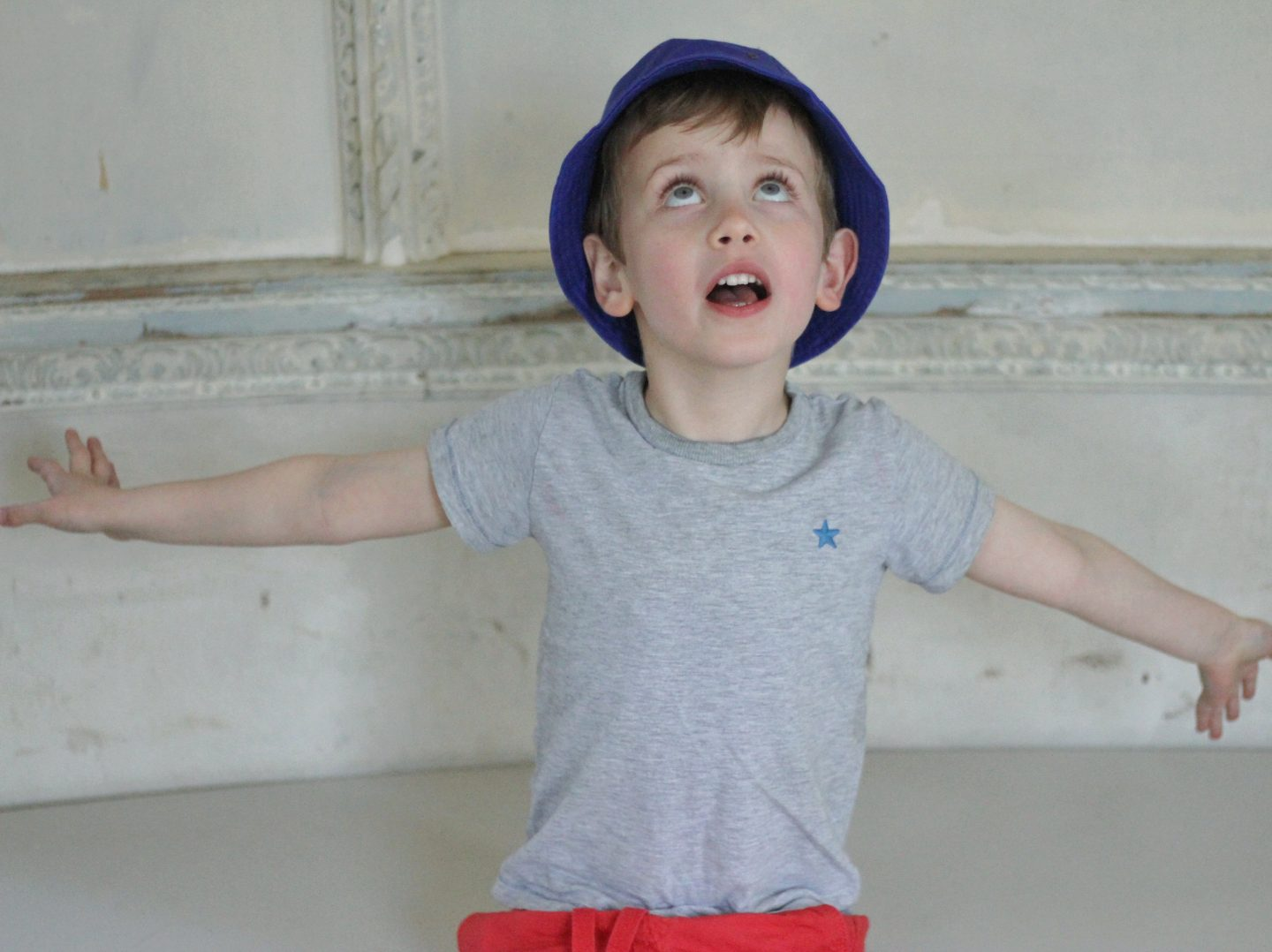 A boy with his arms spread wide, looking up at the ceiling of the Rotunda at Croome