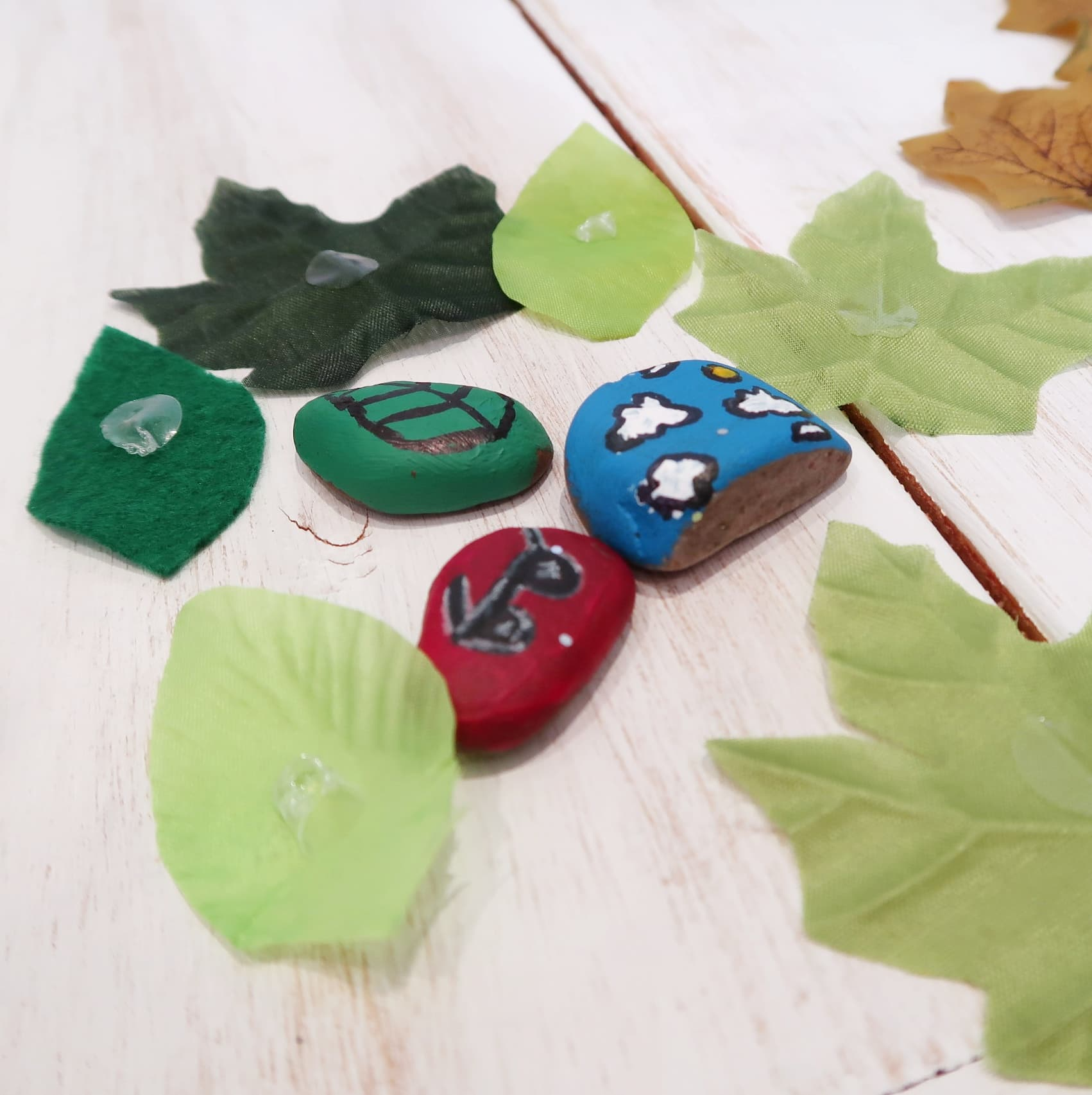 Season craft summer themed pebbles and green leaves