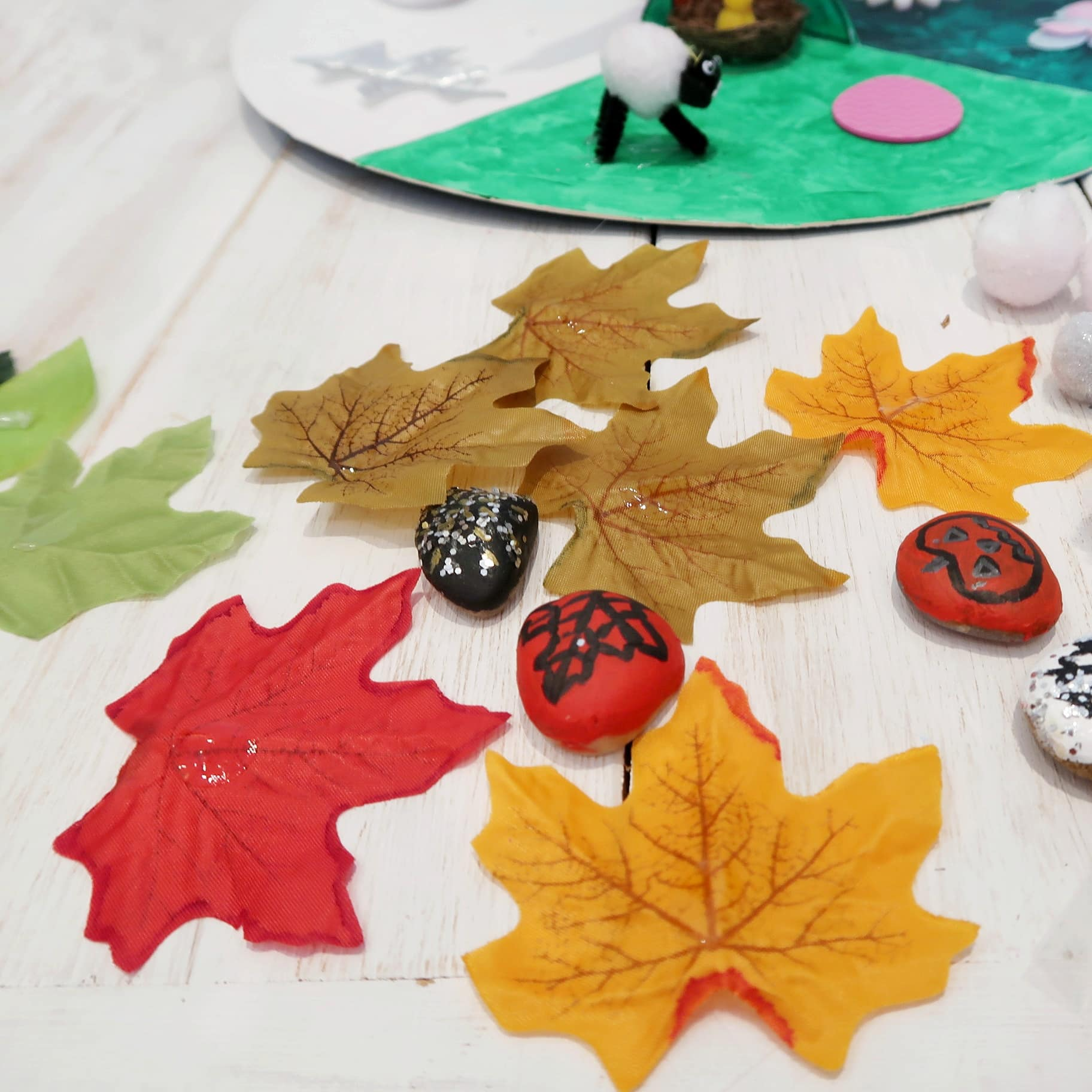 Season craft - Autumn themed painted rocks with a pumpkin, fireworks and a fallen red leaf