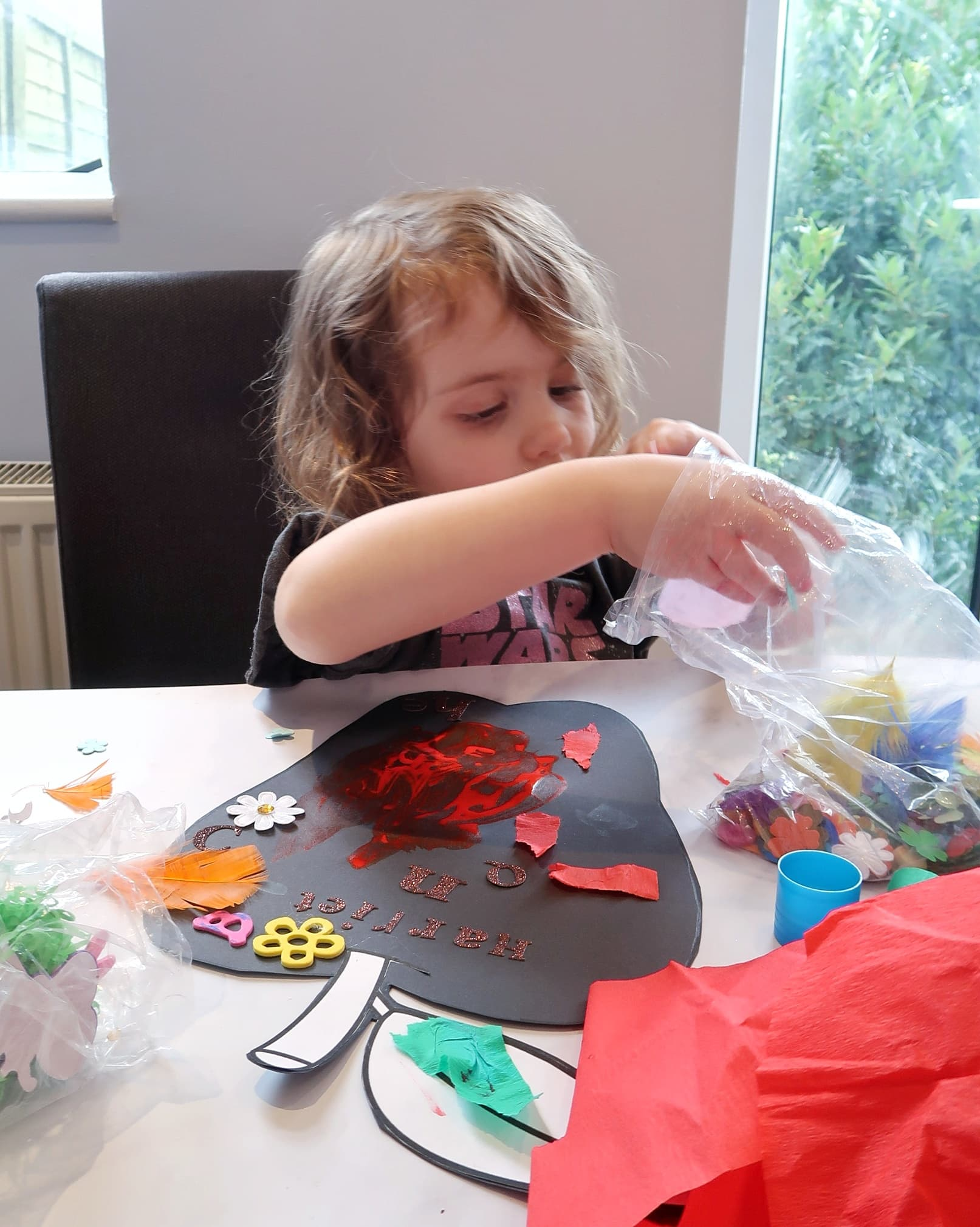 Small girl searching through a bag of letters and beads for back to school craft
